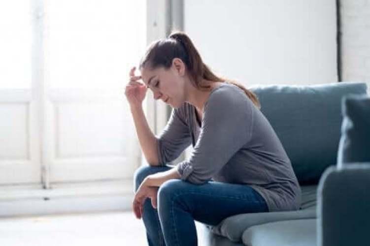 Une femme assise et pensive.