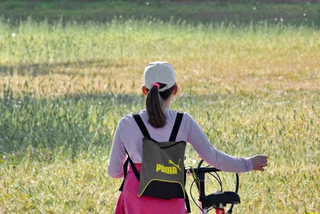 femme fait du vélo dans la nature au milieu des graminées sauvages