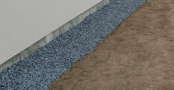 bande de propreté en gravillons avec une bordure autour de la maison pour protéger l'enduit