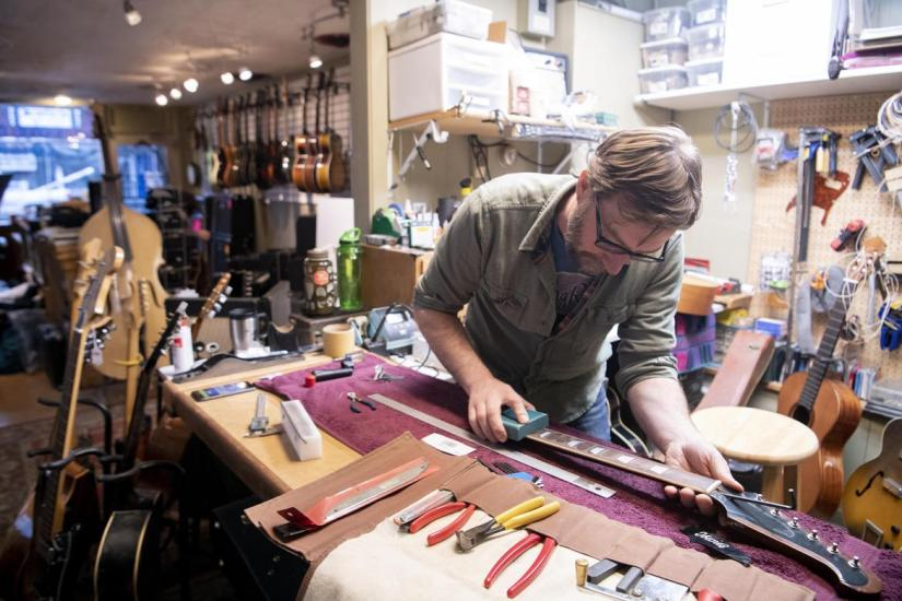 Proprietor and luthier Eben Cole carefully levels the fretboard of a vintage electric guitar at Cole Music Co. at 816 W. Garland Ave. (Jesse Tinsley / The Spokesman-Review)