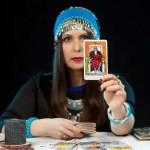 タロットカードを一枚みせる女性占い師