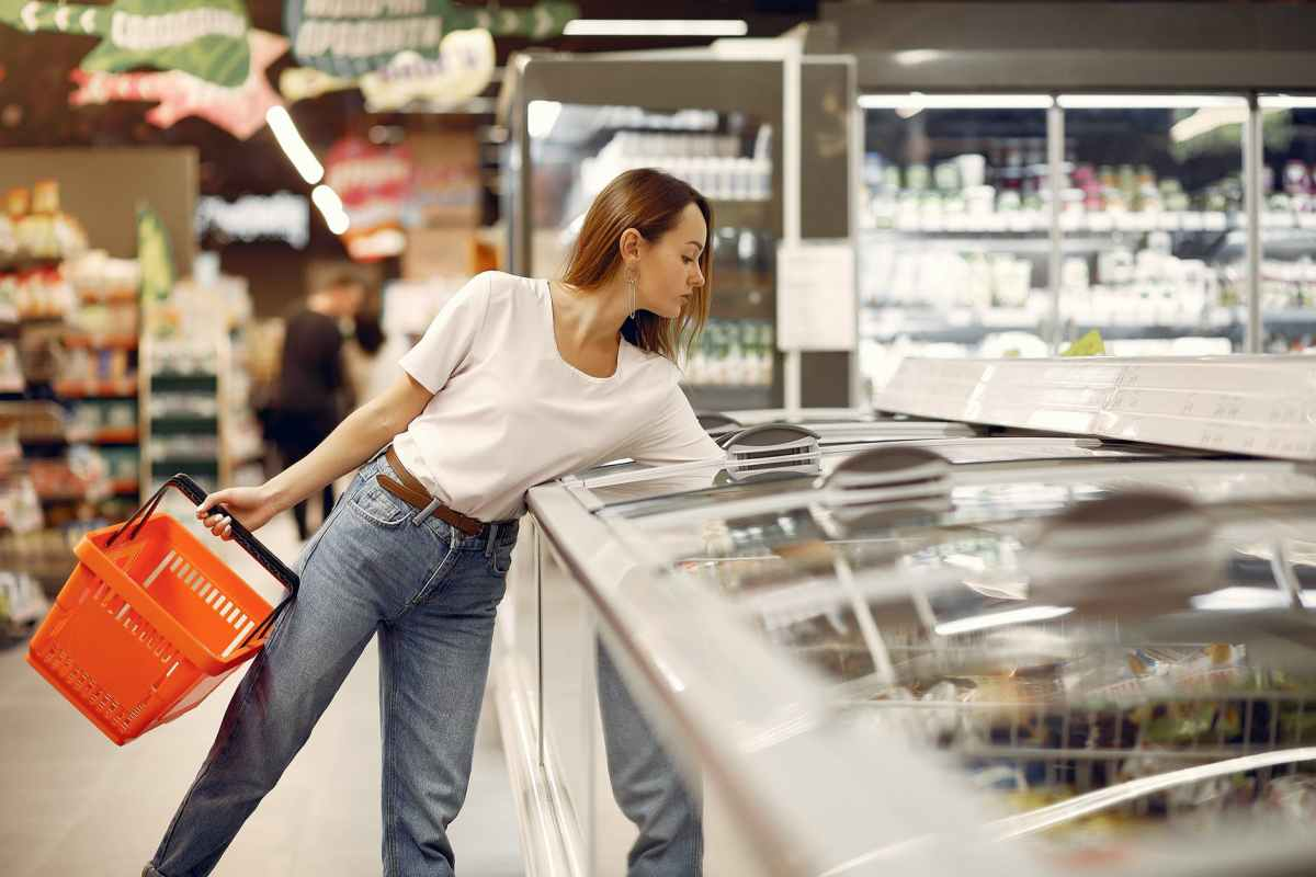 young woman selecting purchases in supermarket