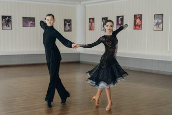 Professional dancers dancing in ballroom. Latin. Young boy and girl