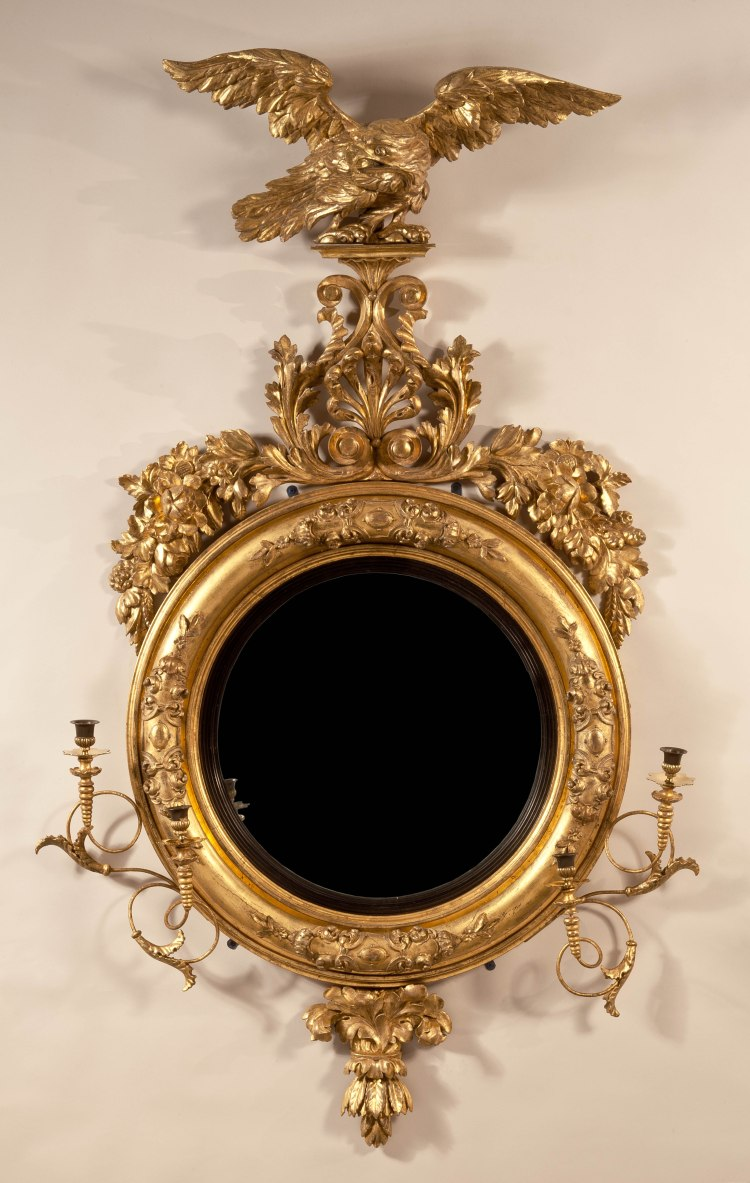 "Regency Convex Girandole Mirror: A carved eagle with spread wings on a tapering platform above scrolled foliage and a pierced anthemion above a convex glass surrounded by an ebonized mirror slip and gilded frame decorated with gilded compo decoration and a foliate pendant, flanked by  pairs of candle arms. H: 67""  D: 31"""