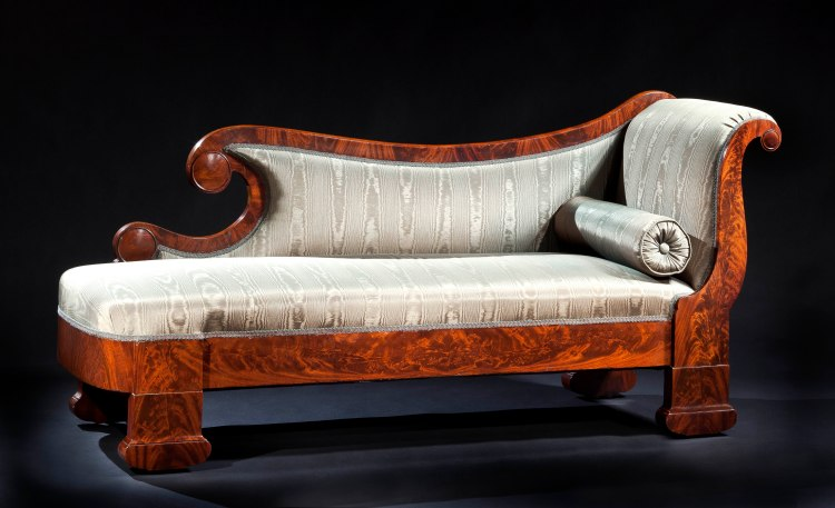 "Plain-Style Grecian Couch by Duncan Phyfe: The undulating veneered crest rail terminating in a scroll with a characteristic rimmed disk boss above an upholstered back and seat with a scrolled arm at one end with a matching rimmed disk boss in the volute. The highly figured seat rail raised on flat rectangular legs terminating in suppressed demilune feet with recessed casters.  H: 34"" L: 74""  D: 24"""