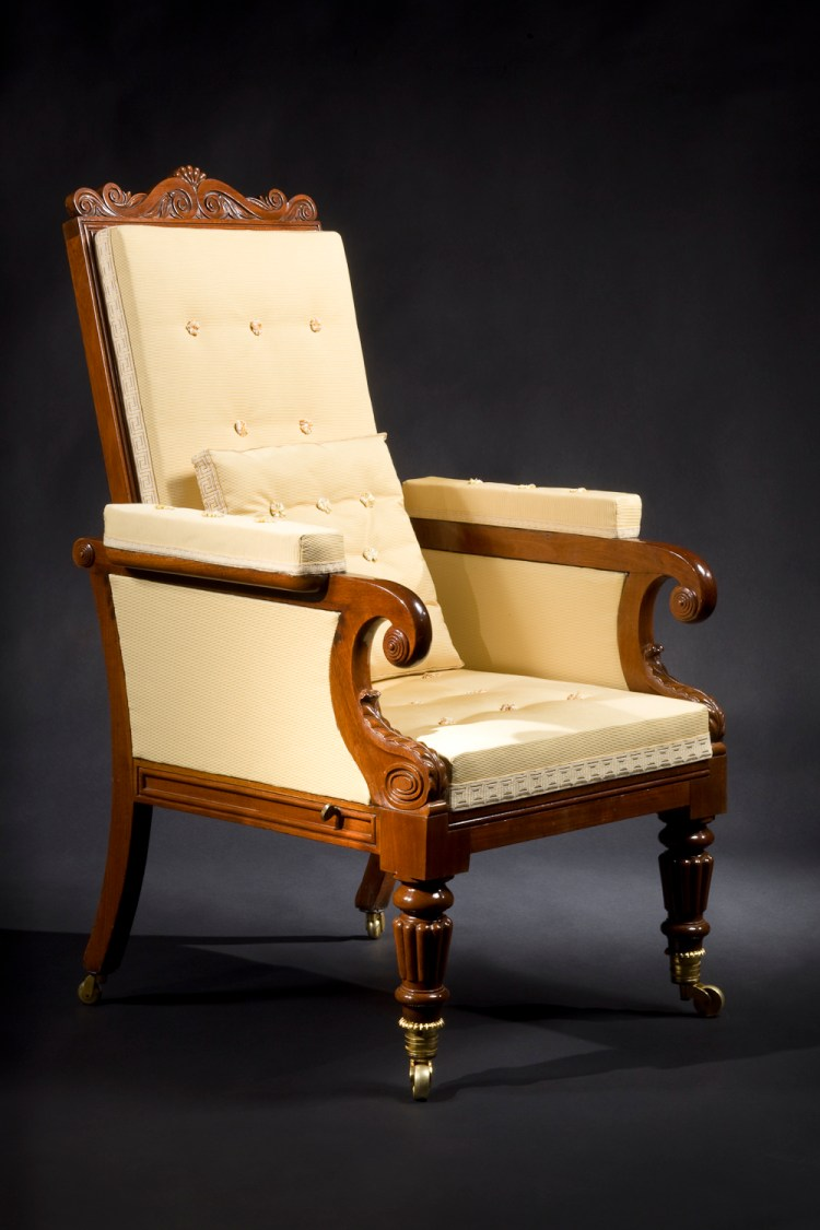 "Classical Mechanical Easy Chair: The lotus-carved arched crest rail above a beaded frame holding an upholstered back, hinged at the base, allowing the back to recline as the upholstered seat slides forward. The padded arm rests terminating in scrolls decorated with tiered, concentric bosses and supported by water-leaf carved scrolls, above turned and reeded front legs terminating in important gilt bronze cup casters. The rear saber legs having brass caster wheels.  H: 46½"" W: 27¼""  D: 29"""