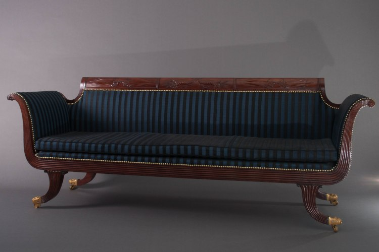 "Classical Scrolled-back Grecian Sofa by Duncan Phyfe: The scrolled crest rail with a central panel with bas-relief carved intertwined cornucopia issuing fruit and wheat, flanked by panels with carved ""thunder bolts"" in a bow knot, the reeded arms with carved rosettes at the ends continue to a reeded seat rail raised on reeded saber legs with brass paw feet on casters. H: 34¼""  W: 90""  D: 23"""