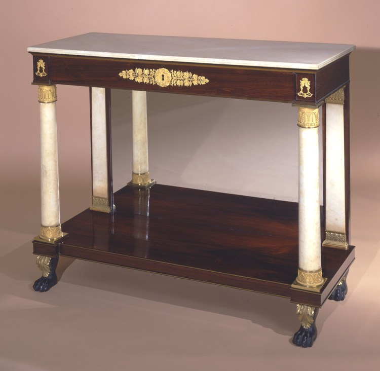 "Classical Bronze-Mounted Pier Table: The oblong white marble top with reeded edge above the conforming rosewood frieze with brass string inlay and a central gilt-bronze foliate appliqué and appliqués over the columns.  The white marble columns with very fine cast gilt-bronze capitals and bases with marble pilasters in the back with carved gilt-wood capitals and bases flanking a mirror plate on an oblong plinth with brass beading on its top and bottom edge, raised on four acanthus-carved animal paw feet with verde-antique paint.  H: 39""  W: 48""   D: 19½"""