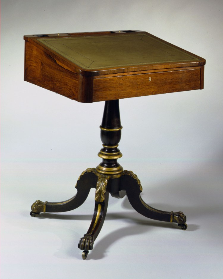 "Rosewood Painted Pedestal Desk: The inclined inset leather top crested with a storage well comprising lidded compartments and a pen rest above a rosewood case with a long drawer on the shallow side and a candle slide at the deep side.  The case is supported on a turned faux-rosewood, grain-painted, baluster-form pedestal with gilded ring turnings and raised on four carved, gilded and rosewood grain painted hocked saber legs terminating in carved and gilded paw feet with brass casters.  H: 31""  W: 24½""  D: 21½"""