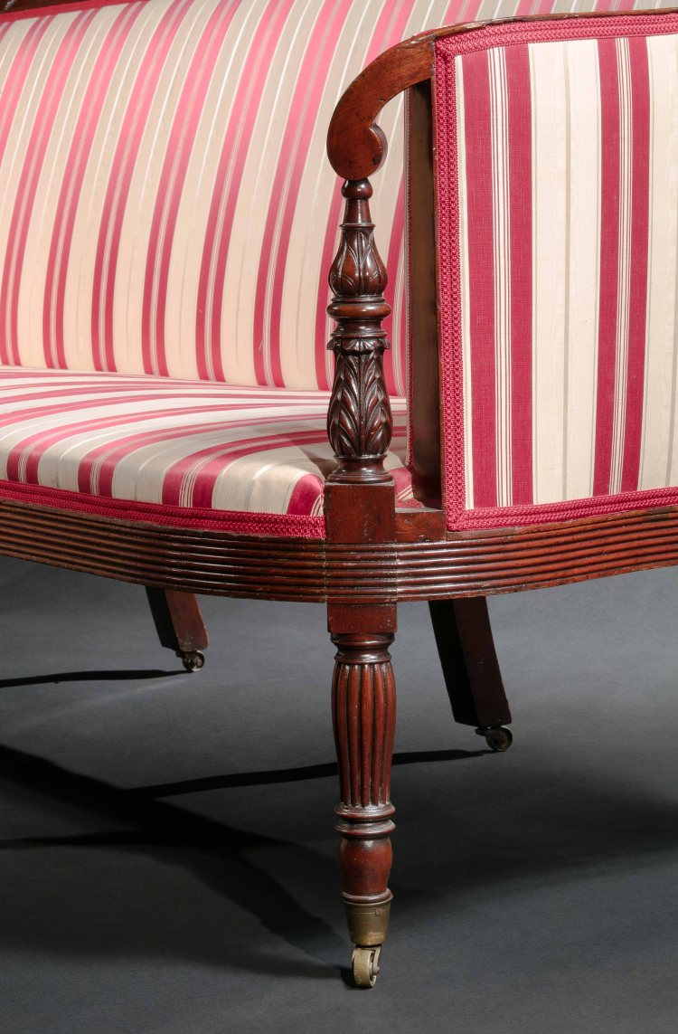 Sofa Carved Arm-rest Support Detail showing arms scrolled at the terminations, supported by a acanthus-carved baluster and leaf-carved standards continuing past the reeded balloon seat to turned and reeded vase-form legs with a ring turnings at the top and terminating in vase-form feet with brass ferule socket casters.