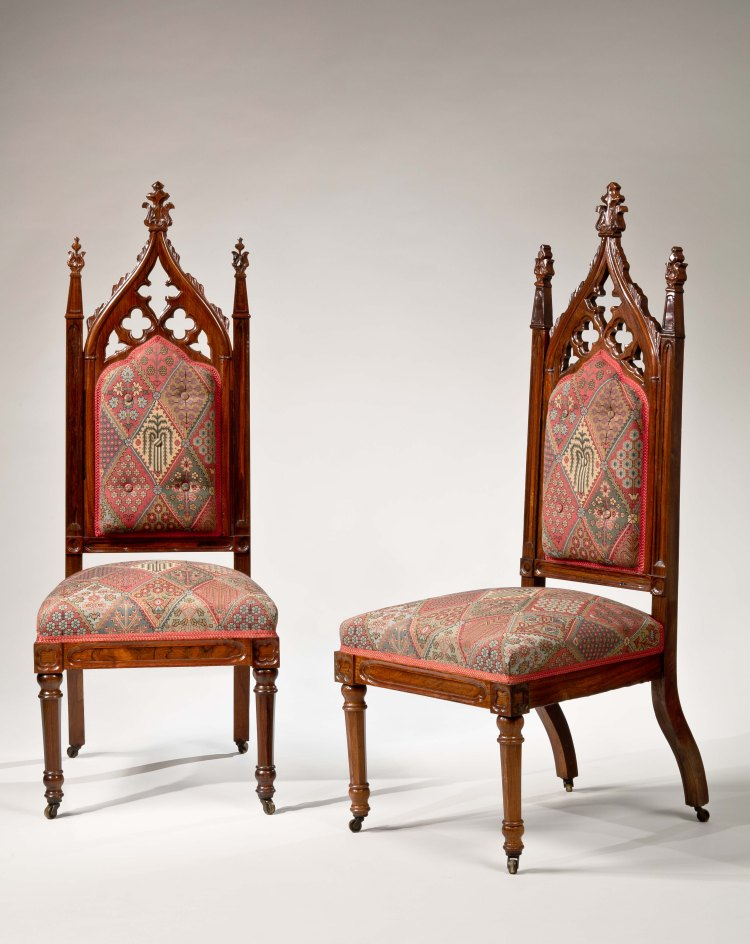 Pair of Rosewood Gothic Revival Slipper Chairs: The pierced Gothic arch with quatrefoils and milk-thistle finial forming the crest of the upholstered back flanked by milk-thistle finials topping the Gothic-paneled styles, continuing down to an upholstered seat and dramatically shaped rear legs.  The Gothic-paneled seat rails with quatrefoils above the faceted, turned front legs terminating in brass casters.