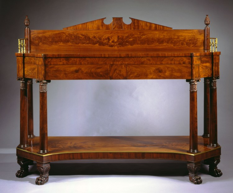 """Classical Carved Mahogany Sideboard: The backsplash with a broken arch pediment with flanking carved pineapple finials above an oblong mahogany top with canted front corners and brass gallery sides above a conforming case with two short and one small central drawer supported by pairs of columns with carved Ionic capitals at the canted corners, resting on a concave-shaped shelf with brass beading, raised on pairs of canted, carved paw feet corresponding to the columns above.   H: 56¼""""  W: 71¾""""  D: 22"""""""