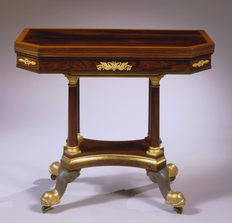 "Classical Bronze-Mounted Rosewood Card Table: The cross banded oblong swivel-top with canted corners opening to a banded felt playing surface. The frieze, under a knife edge molding, boasting a central gilt-bronze mount with two facing swans and two gilt-bronze foliate mounts on the canted corners. A star stamped brass filigree band inlaid in ebony wraps the lower edge of the frieze. The case is supported by four columns with gilded Doric capitals and bases and rests on a concave shaped and molded plinth with brass string inlay. The plinth is raised on carved gilt and vert-antique painted dolphin feet with brass casters. H: 29¾""  W: 36""  D: 18"""