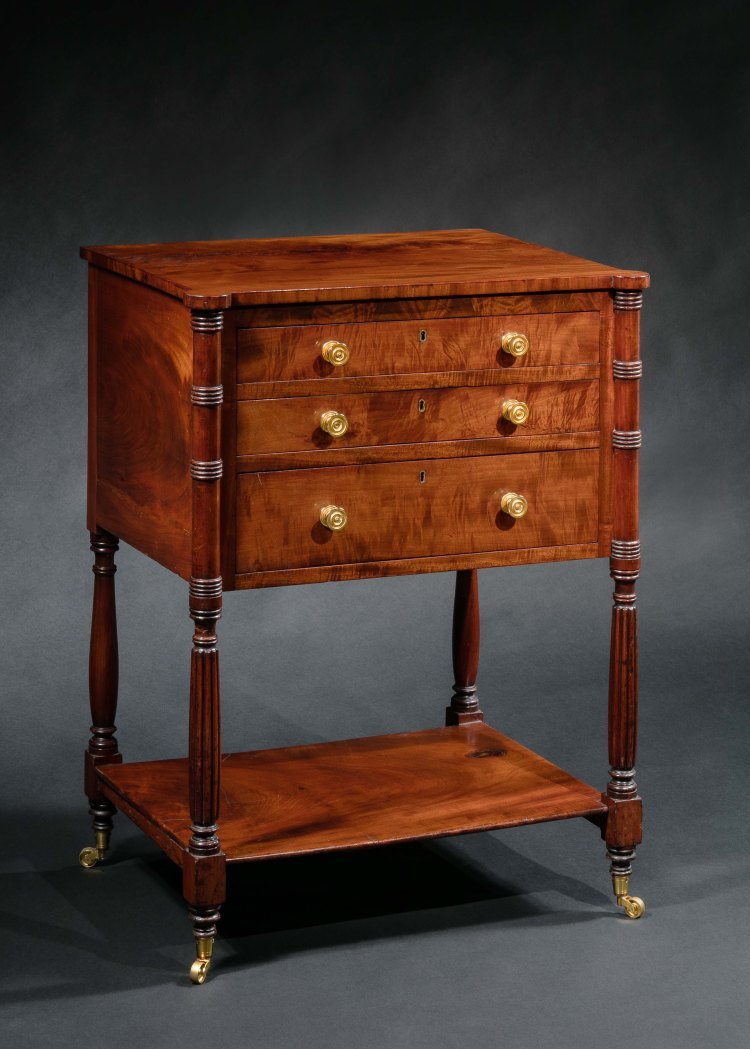 """Federal Occasional Table: The rectangular top with out-set """"cookie corners"""" above a conforming case with three drawers, the top drawer with adjustable writing surface retaining original baize writing surface framed with gilt-stamped leather border and separate compartments for ink well, sander and pen cradle. The second drawer is fitted with small compartments. The case is raised on turned and reeded legs holding a low shelf, raised on turned feet and brass cup casters.  H: 30¾""""  W: 22¾""""   D: 17"""""""