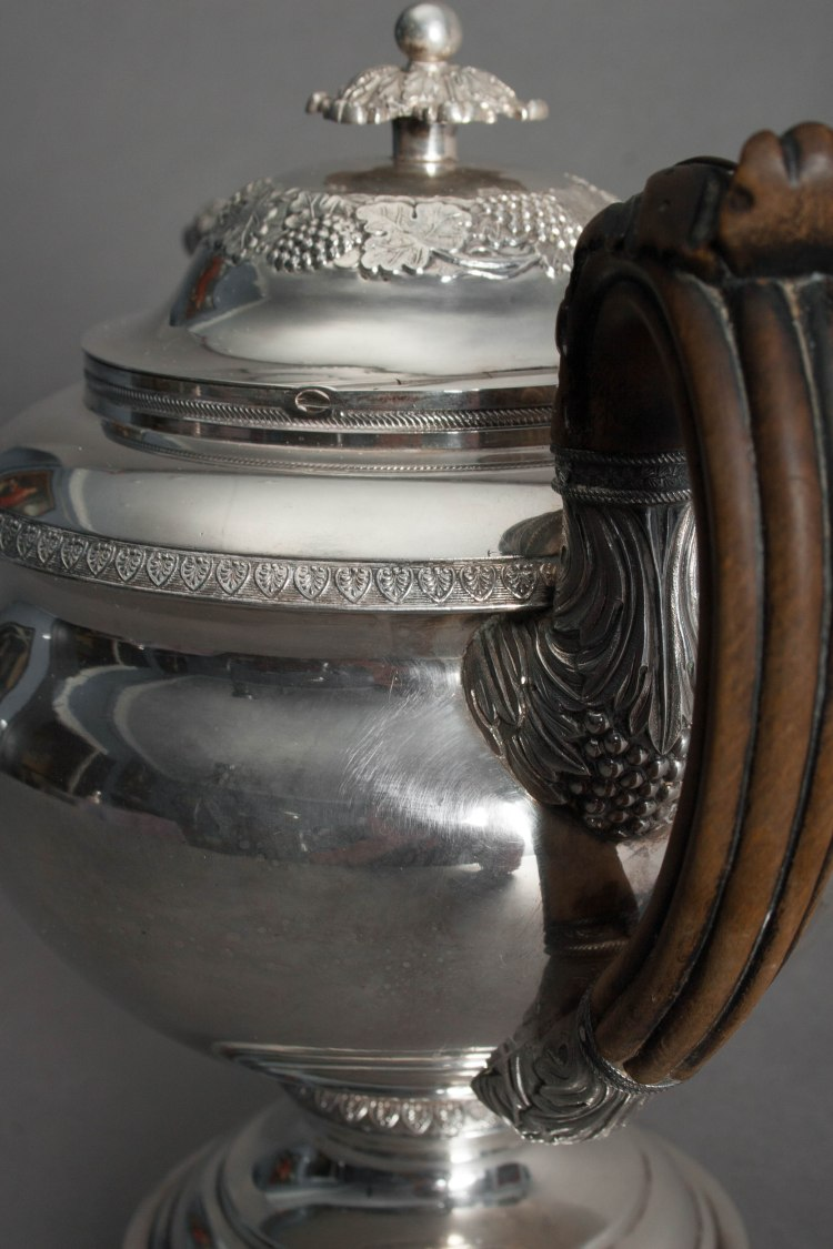 Silver Tea Service by Fletcher and Gardiner: Detail of one Tea Pot showing carved wooded handle, hinged lid with leaf finial, repousse decoration and stamped banding.