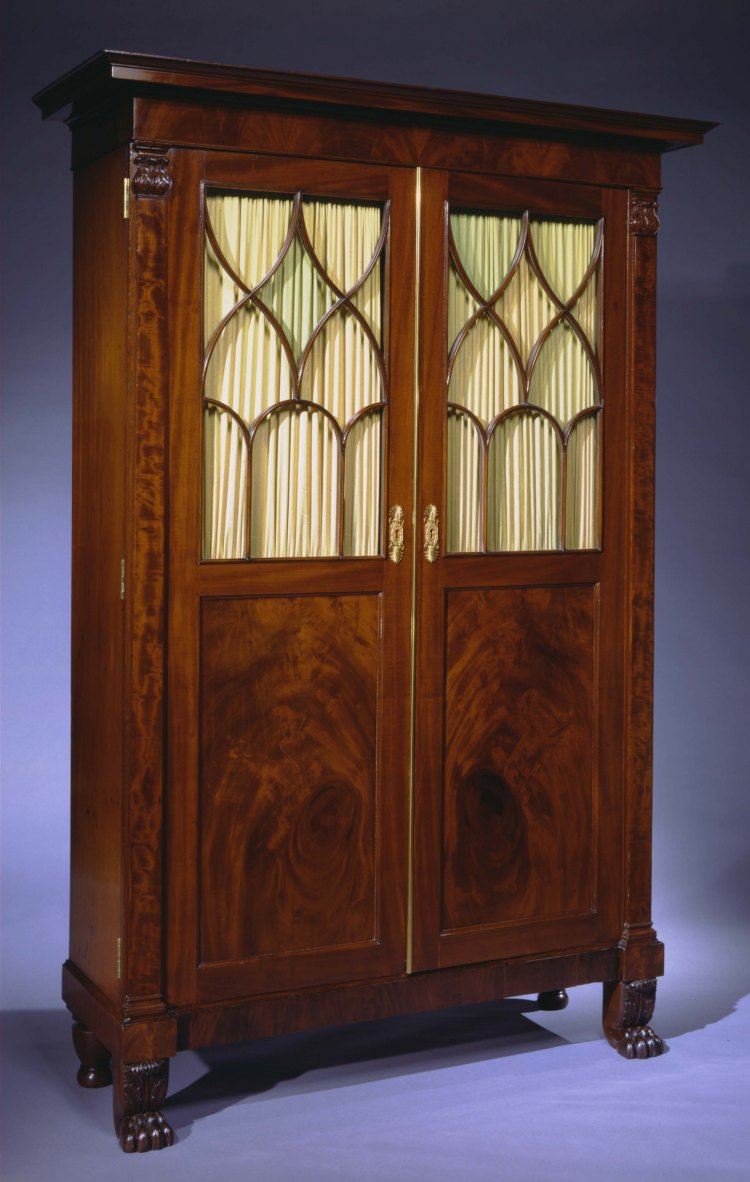 Cabinet Secretary Bookcase by Duncan Phyfe:  Bookcase Cabinet with Desk interior with flat oblong pediment top over a tall case having a pair of paneled cabinet doors with glazed arched and Gothic tracery windows in the top half flanked by pilasters with acanthus carved capitals, opening to a bookcase with four adjustable shelves bisected by a fall front secretary section with stacked short drawers with original stamped brass pulls flanking the fall front writing surface, all resting on a base raised on acanthus carved animal paw feet and turned legs in back.