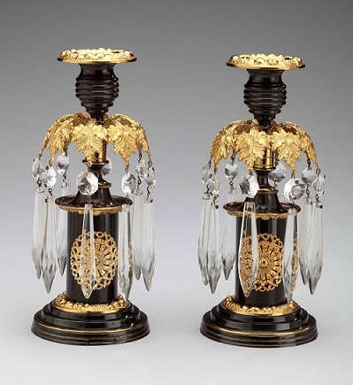 Pair of Regency Candlesticks of lacquered brass with Glass Prisms, each with a single candle cup above a canopy of leaves from with the prisms hang above cylindrical plinth bases.