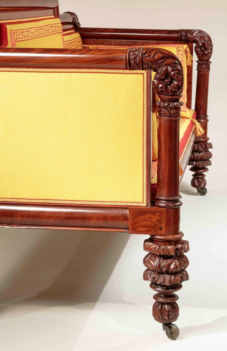 Carved Mahogany Box Sofa side view detail showing elaborately carved scrolled hand rest continuing to a columnar support above elaborately carved legs.