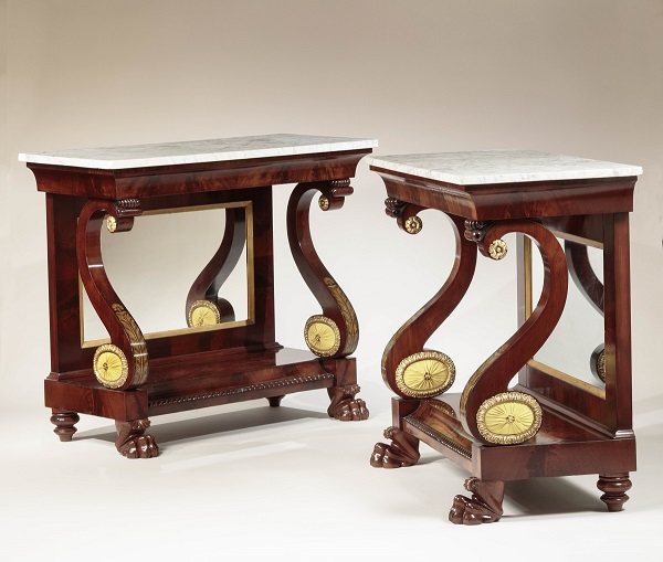 """PAIR OF Gilt-Stenciled Mahogany PIER TABLES: Each with oblong Carrara marble tops with conforming cavetto frieze with gilt-stencil decoration, supported by scrolled supports with upholstered oval bosses with carved gilt-wood frames, flanking a mirrored back, the mirror bordered by gilt beveled liner, on a plinth with a concave and gadrooned front edge, raised on acanthus-carved feet. H: 37"""" W: 44""""  D: 20¾"""" each"""