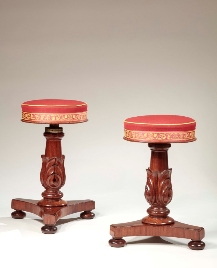 Pair of carved mahogany Piano Stools the pedestals carved with bold acanthus leaves, raised on tripartite plinths on pad feet.  The seats with red upholstery banded with red and gold passementrie tape. Adjustable height.