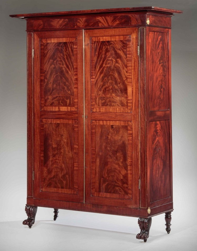 Classical Armoire or Wardrobe with the flat projecting cornice over a knife-edge molding above a case with pilasters with brass string inlay flanking a pair of highly figured, paneled and cross-banded cabinet doors with brass hinges and astragal, opening to a vertically bifurcated interior with the capacity for five shelves per side. The case is raised on a plinth with acanthus carved hairy paw feet in front and short turned legs in back.  All four feet are raised on period casters.  Construction notes: The back is comprised of four pine raised panels.  The case is joined by bed bolts, top and bottom.
