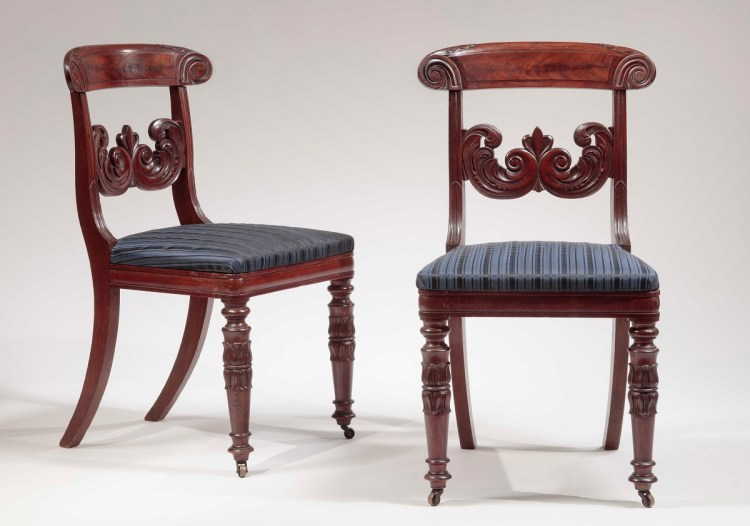 "Pair of carved mahogany dining chairs, each chair with a bowed crest rail with acanthus carving along the top edge and terminating at each end with relief-carved scrolled ""ram's horns"" continuing to grooved styles holding a foliate carved stay rail centering an anthemion, above an upholstered slip seat on a bolection-molded seat rail raised on turned, tapering legs with lotus carved decoration, on metal casters and saber legs in back."