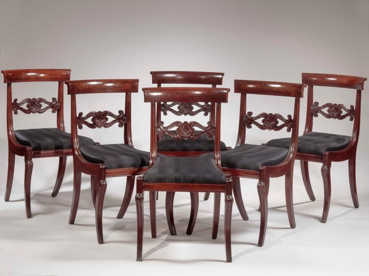 Set of six carved mahogany dining chairs, the crest rail inlaid with flame mahogany veneer framed with ebony stringing above a carved stay rail above an upholstered slip seat continuing to saber legs.