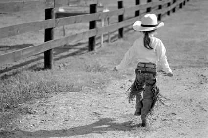 Four-year-old cowgirl Jess Abney skipping along the fence.