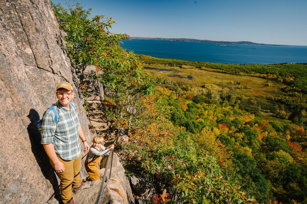 family with kids hiking through fall foliage on precipice trail in acadia national park