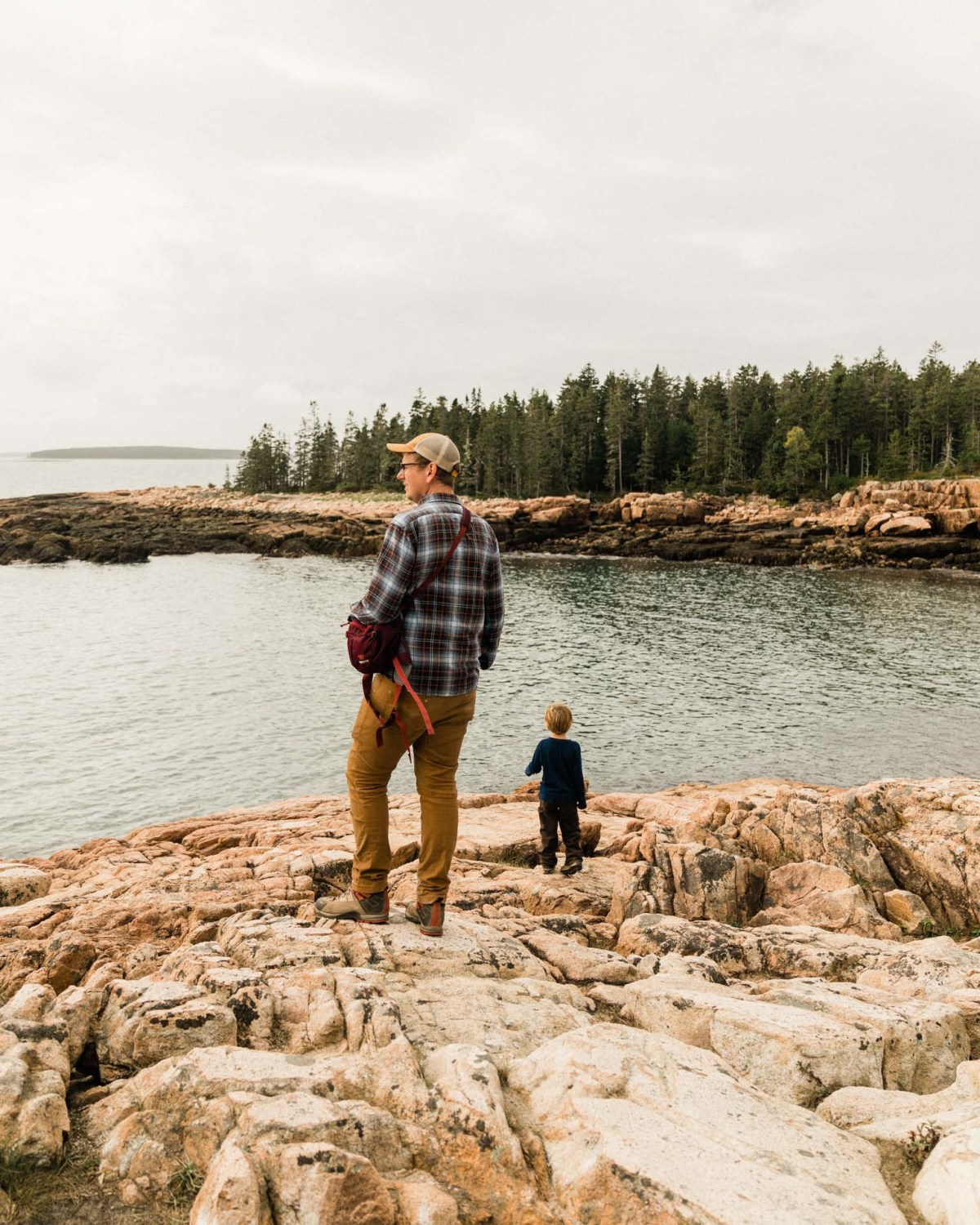 family with kids hiking on the rocks at acadia national park