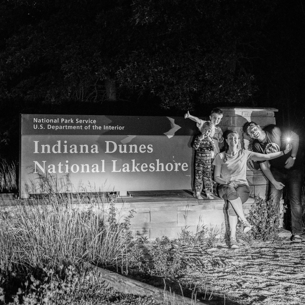 traveling family in front of Indiana Dunes National Park sign