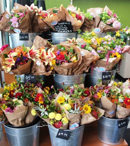 """A huge variety of Northwest-grown mixed bouquets labeled with """"American Flowers Week"""" at New Seasons Market."""