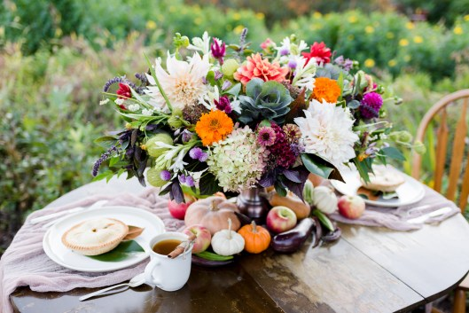 The sweetheart table is embellished with seasonal vegetables, gourds and pumpkins, as well as local pies and local flowers in Kelly's gorgeous centerpiece.