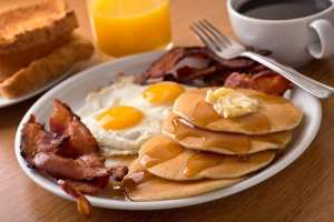 Large breakfast of pancakes with butter & syrup, sunny side up eggs, bacon, coffee, orange juice, and toast