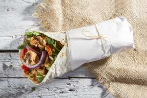 Grilled Chicken Kebab Doner Wrap with onion, parsley and tomato on rustic white painted wood table.
