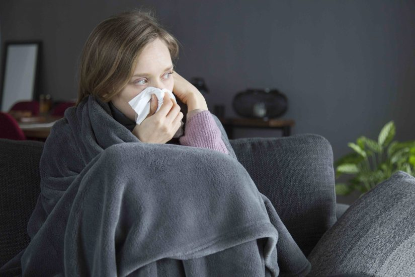 Bored sick young Caucasian woman covered with grey blanket sitting on grey sofa in living room, looking aside, holding one hand at head, blowing nose with napkin. Illness, pain concept