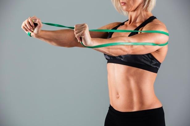 Aunque este ejercicio para tonificar brazos parece muy simple, trabaja tríceps y hombros al hacer press de pecho con la banda.