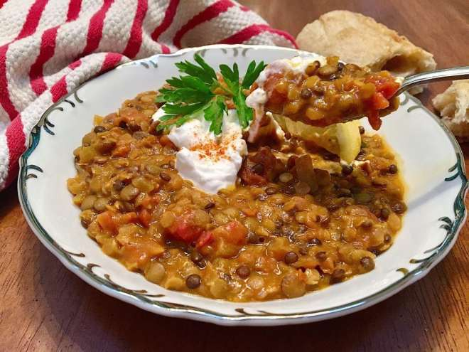 spicy lentil curry in a white bowl, topped with yogurt and parsely with a spoon dipping into it.