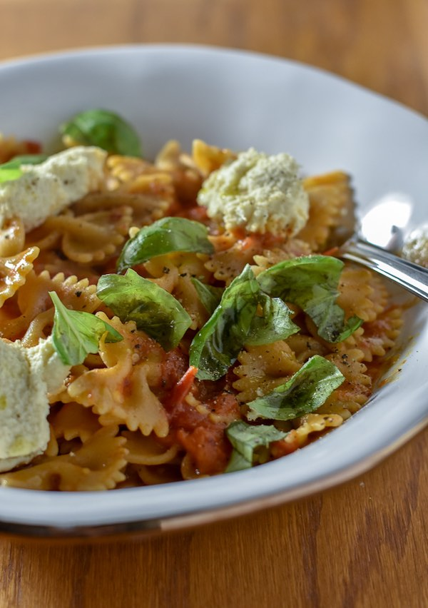 Farfalle pasta with fresh tomatoes and ricotta in a white bowl, garnished with fresh basil