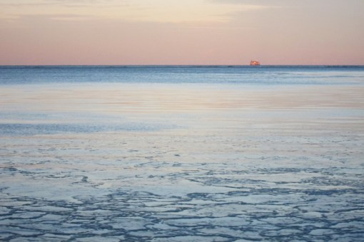 The watery, icy expanse of Lake Michigan under a sunset sky.  A pink building glows on the horizon.