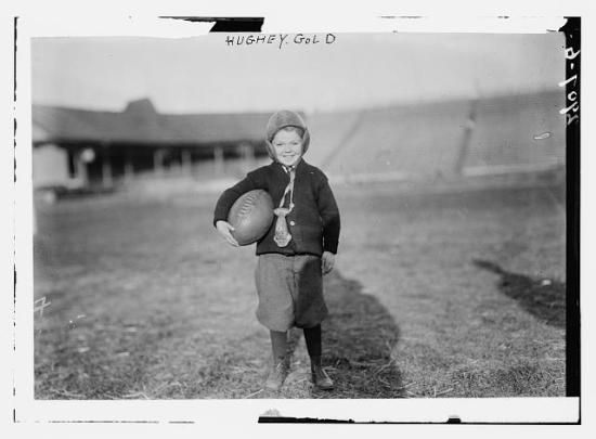 a young boy holds a football under his arm.