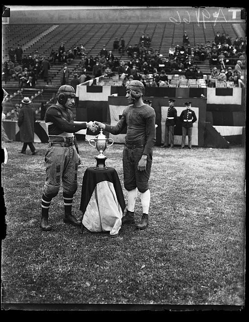 Black and white photograph of 2 football players shaking hands at the trophy stand.