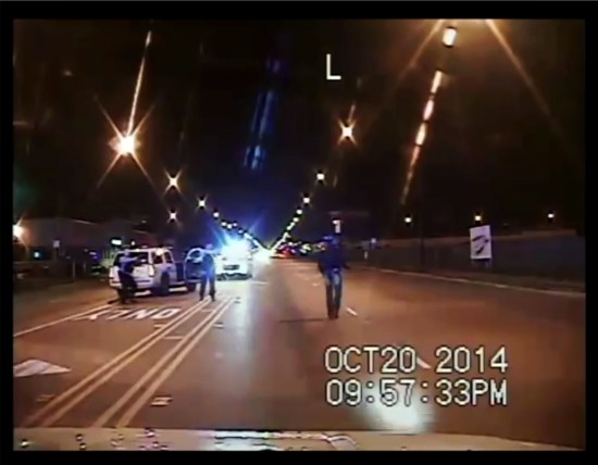 Screen shot of Officer Jason Van Dyke raising his weapon to shoot Laquan McDonald on a Chicago street.