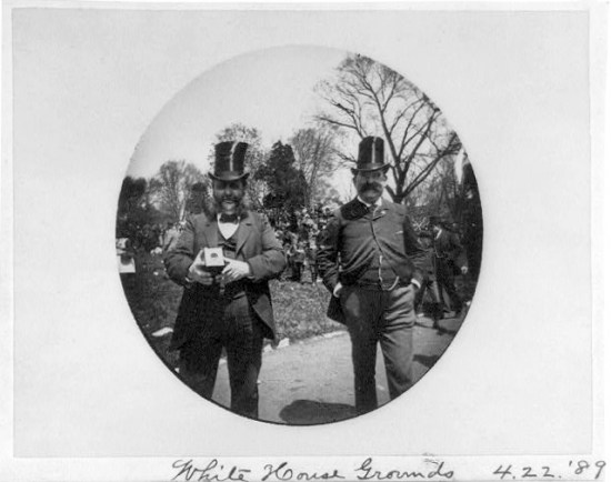 Two dressed-up men smile into the camera on a spring day. One holds a Kodak camera.