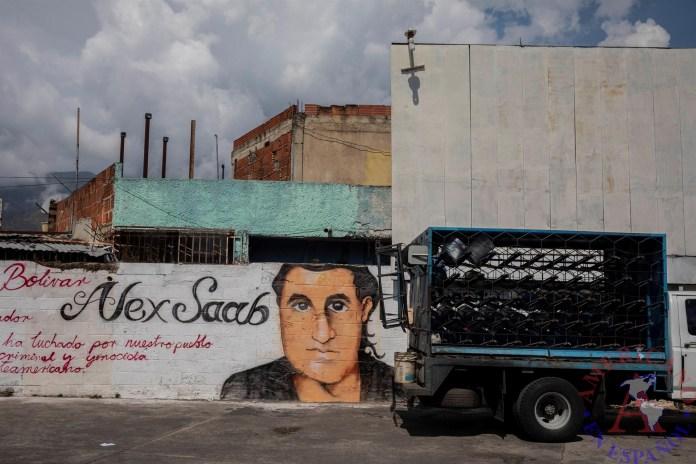 Un pequeño camión pasa junto a un grafiti con la imagen del rostro de Alex Saab en Caracas