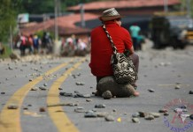 Un indígena espera sobre una roca este domingo durante el bloqueo de la vía panamericana en el municipio de Caldono