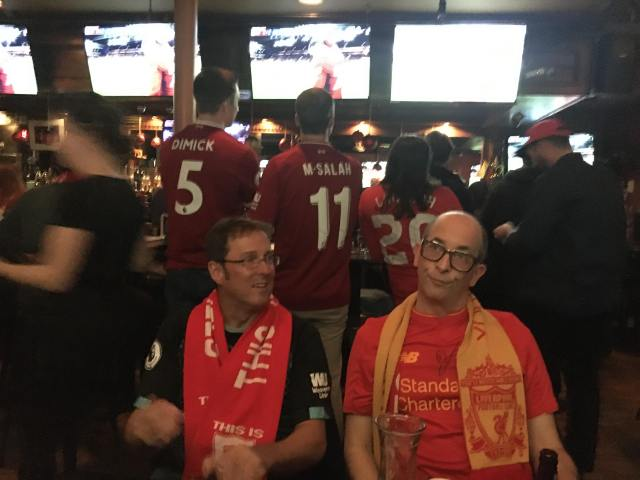 Author and guest at a bar watching soccer
