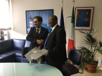 Francesco la Camera and Mamman Nuhu sign the agreement.