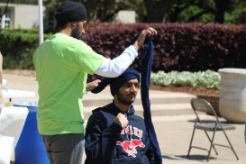 """SMU Sikh Students Association President Parminder Deo ties a turban around student Alli Schloeman."" (source: Christopher Saul / The Daily Campus)"