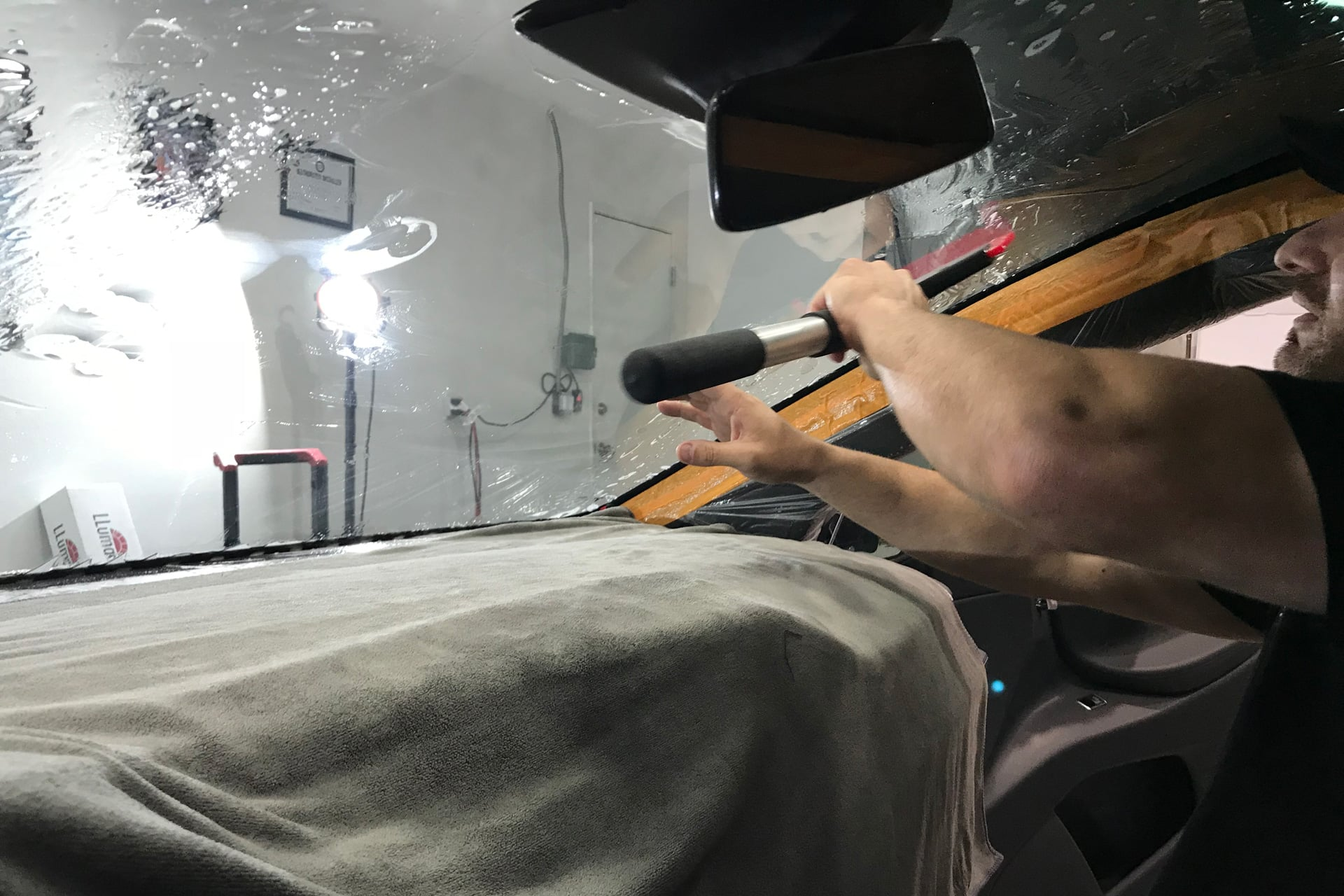 Tyler O'Hara installing window tint on Tesla model